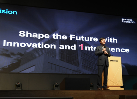 A man is giving a presentation on stage under the slogan of 'Shape the Futher with Innovation and 1ntelligence.'